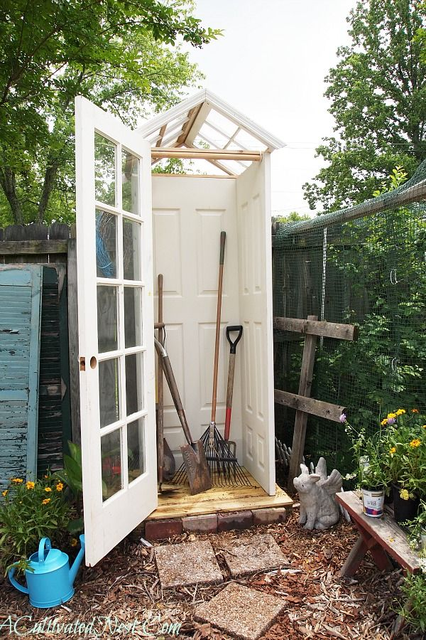 DIY garden tool shed made by repurposing old doors and windows.