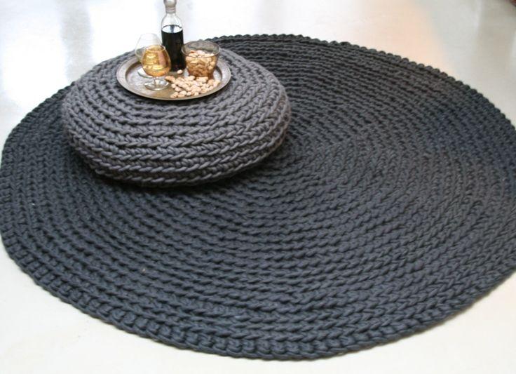 Soft round rug, crocheted of dark grey thick wool.