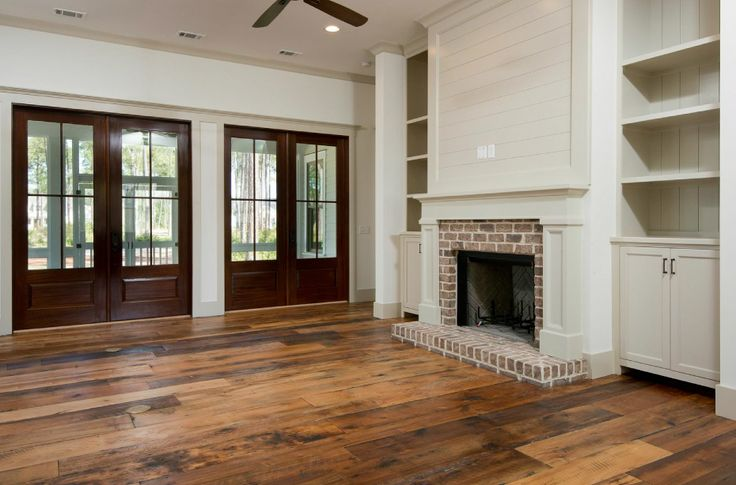 Family room with brick fireplace, custom built ins, stained wood doors and reclaimed wood floors.