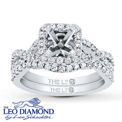 This engagement ring setting features brilliant round Leo Diamonds that frame the center and line entwined waves to form the band. Additional Leo Diamonds accent either side of the profile while more Leo Diamonds trace the matching contoured wedding band to complete the look. Crafted of 14K white gold, the bridal setting has a total diamond weight of 3/4 carat. The diamonds are independently certified by Gemological Science International and GemEx for their authenticity and exceptional b...