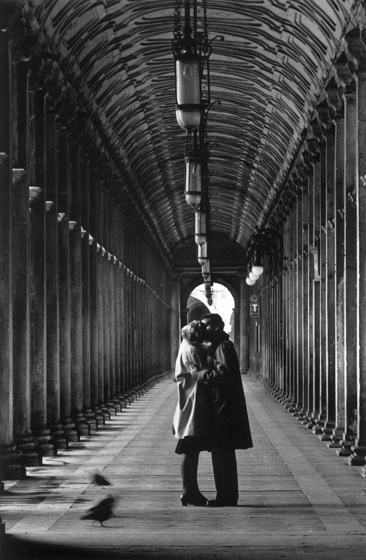 Gianni Berengo Gardin, Venezia 1959, Piazza San Marco «Un bacio a Venezia. Un gesto d'amore di assoluta bellezza fermato all'alba nella città deserta. Un bacio lungo, appassionato, intenso: lo rivelano i piccioni, mossi e sfocati per il tempo lungo che ho dovuto usare per la poca luce. Ma la vera luce veniva da quegli amanti perduti nel loro amore»
