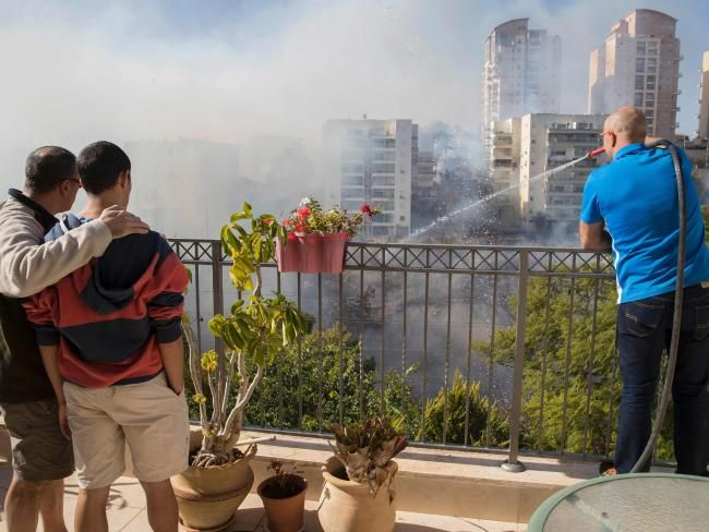 Two Israelis watch as another tries to extinguish a fire with a hose from a rooftop in the northern Israeli port city of Haifa. Picture: AFP/Jack Guez