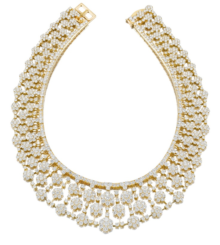DIAMOND NECKLACE, VAN CLEEF & ARPELS, 1980S.  Designed as a flexible collar of graduated flowerhead clusters set with brilliant-cut diamonds, mounted in yellow gold,    signed Van Cleef & Arpels and numbered, French assay and maker's marks, fitted case by Van Cleef & Arpels.