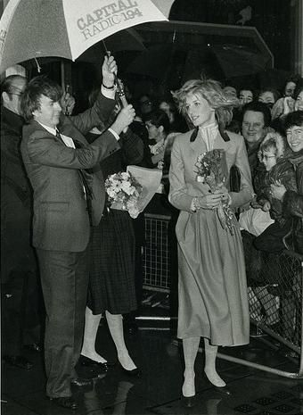 November 23, 1982:  Princess Diana receives shelter under an umbrella during a visit to Capital Radio in London.