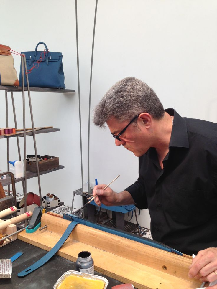 A leather worker painting the edge of a piece of leather which will go on to be part of the iconic Birkin bag.