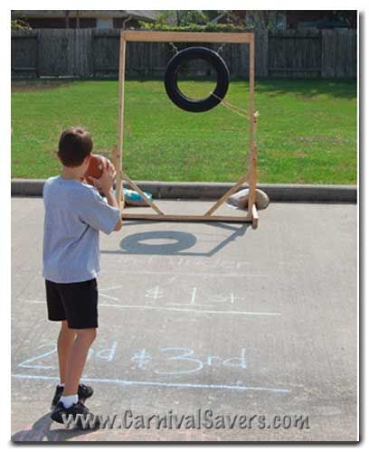 """Football Toss: Handmade Goal (see example above) made from a wood frame supporting a tire.  Sidewalk Chalk (or other marking material) to draw lines for different aged players (notice photo above) Foam footballs for tossing – at least 6 or more Carnival Prizes – consolation, and others (depending upon how you set up this carnival game) sports themed carnival prizes are a great idea for this booth [   """"Football Toss: Handmade Goal (see example above) made from a wood frame supporting a tire…"""