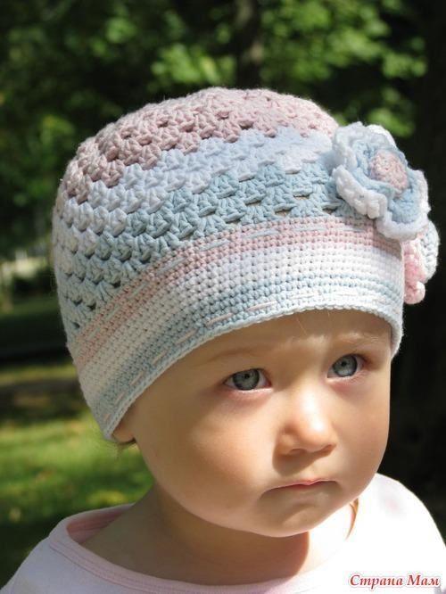 """Bonnet aux couleurs dégradées , orné de fleurs et un bonnet bleu , trouvés sur la page facebook de """" Munequitos A Crochet """" , avec ses grilles gratuites ."""