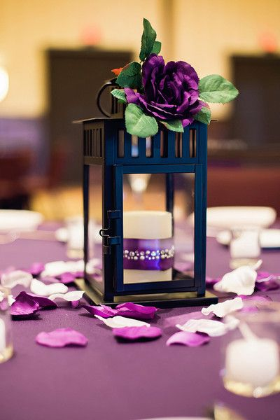 Simple purple wedding reception decor idea - purple table cloths, flower petals, metal lantern + purple flowers {Candid Moments Photography}