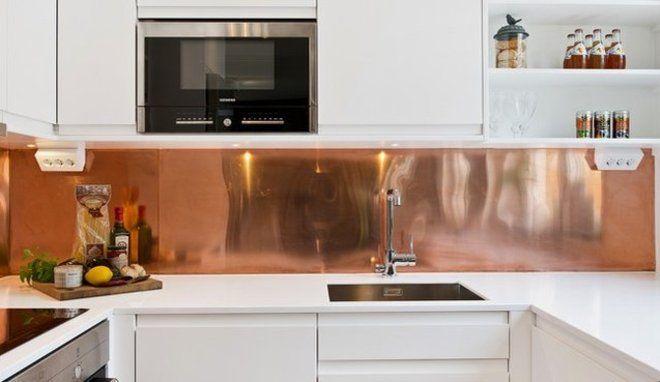 Une cuisine blanche avec une crédence cuivre