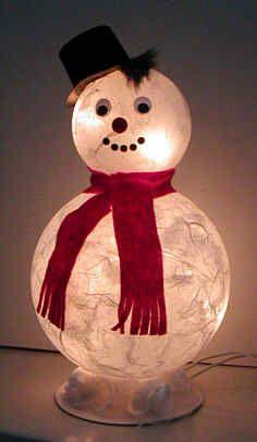 Lustige Schneemänner, die mit einer Lichterkette beleuchtet werden, bringen Licht und Freude in die dunkle Jahreszeit