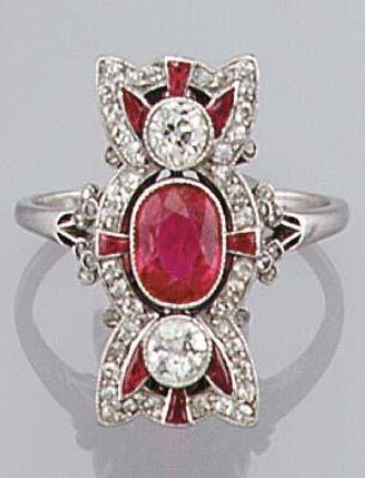 A Belle Epoque ruby and diamond panel ring, French, circa 1910. Of stylised bow design, collet-set with an oval ruby estimated to weigh approximately 1.4 carats, and two circular-cut diamonds in vertical formation, within a pierced border of single-cut diamonds and baguette rubies, with rose diamond flowerhead decoration to the shoulders, French assay mark for platinum used until 1912 and vaguely numbered. #BelleÉpoque #ring