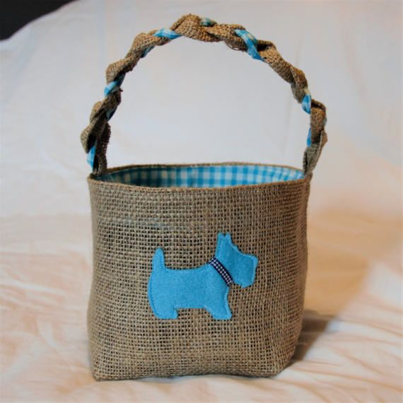 Scottie dog hessian basket. Beautifully handmade basket lined with blue check cotton fabric and decorated with a blue felt Scottie dog. This basket would make an ideal gift. The basket measures approximately 15cm (6 inches) high and 18cm (7 inches) diameter and has a pretty plaited handle. Do you have a bespoke request? Were happy to take on custom projects, please contact us with your requirements.