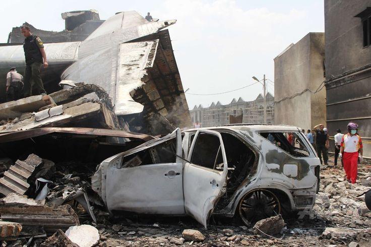 インドネシア・スマトラ島メダンで、墜落・炎上した空軍輸送機の尾翼部分と破壊された車(2015年6月30日撮影)。(c)AFP/ATAR ▼1Jul2015AFP|インドネシア軍機墜落、死者141人に http://www.afpbb.com/articles/-/3053313
