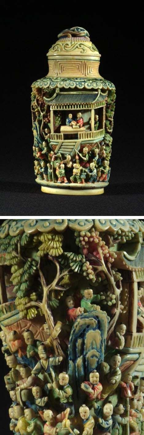Snuff Bottle and Stopper with Spoon, 1800 - 1850, This early 19th century Chinese snuff bottle is made of ivory. It is intricately carved with figures, trees and architecture. The stopper is a dog holding its tail in its mouth. 12.3 x 6.5 cm