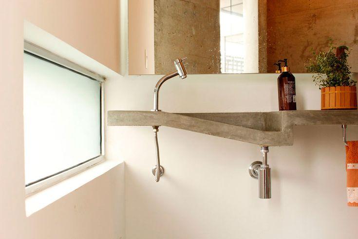 Reforma em apartamento na Chácara Klabin - A bancada do lavabo, construída de argamassa armada, surpreende por não ter uma das laterais, revelando seu perfil ao usuário. As duas janelas horizontais com vidros translúcidos trazem luz natural ao lavabo, e a ventilação natural é fornecida pela janela existente atrás do espelho. ______________________________  Chácara Klabin apartment renovation #bathroom #sink #detail #concrete