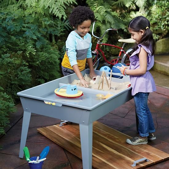 Sand & Surf Table | The Land of Nod - If you can't take your kids to the beach, bring the beach to them. Sand & Surf Table features a sturdy, iron and wood construction and two spacious bins for water and play sand, so your little ones can have a nice day at the beach from the comfort of your own backyard. It even features a protective lid to cover it when not in use.