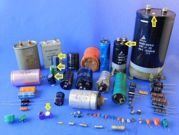 Figura 15 -Capacitores eletrolíticos diversos.  As setas indicam as válvulas de escape.  Os capacitores que formam as duas linhas inferiores da foto são de tântalo.