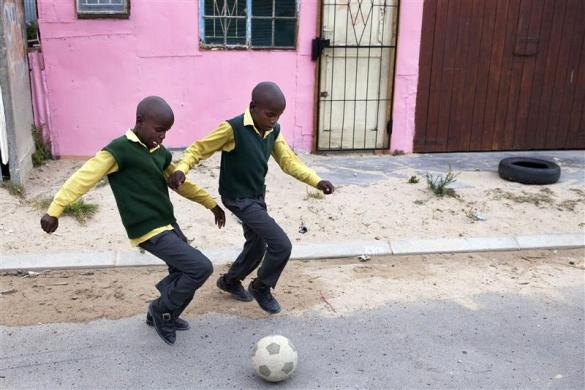 Children play soccer on the street outside their small shack in Cape Town's Khayelitsha township, February 23, 2010.   REUTERS/Finbarr O'Reilly