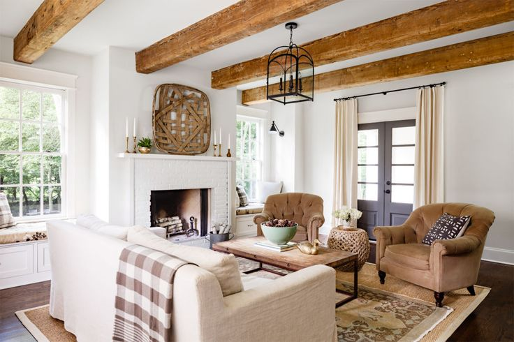 The secret to this inviting Tennessee living room is the top-to-bottom texture, from the scuffed beams to the velvet armchairs to the linen draperies flanking the dark gray doors.