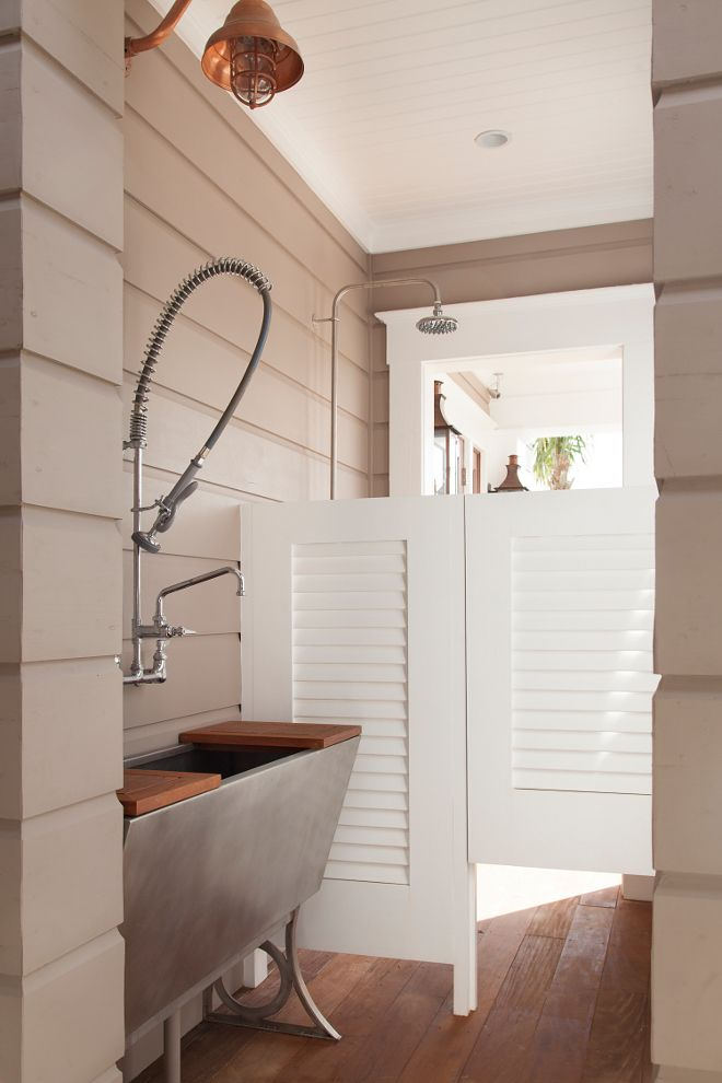 Outdoor shower near the front door and the attached garage. Shingle Style Beach House with Classic Coastal Interiors