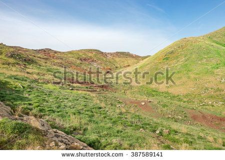 Mountain desert with fresh spring green grass. Mountain plain field / meadow with nice round hills and red soil. Madeira Island, Portugal.