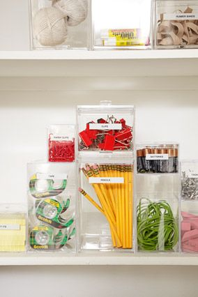 De-Junk Your Junk Drawer  household necessities are stacked in clear, labeled boxes of varying sizes inside a cabinet