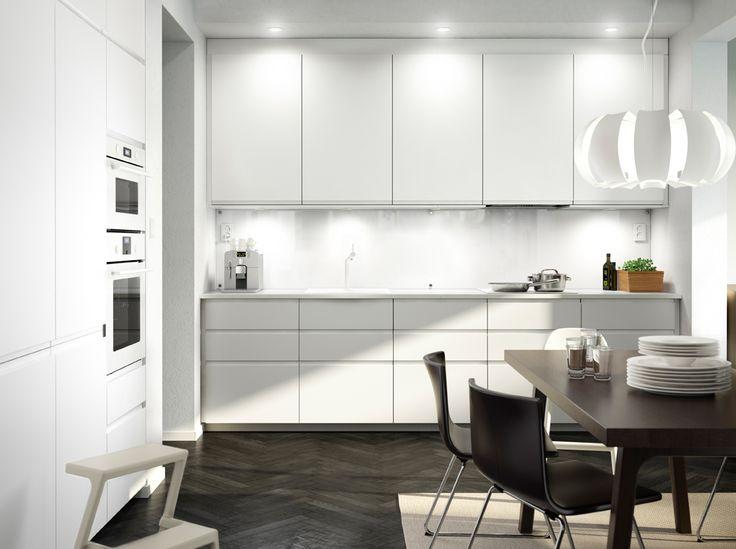 Cocina blanca con electrodomésticos blancos, sillas de cuero y mesa…