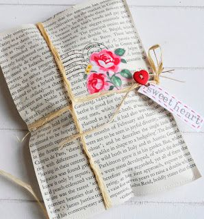 """you place a small gift or some sweets on a piece of paper, place a matching piece on top and machine or hand sew round the two so the gift is enclosed.......then decorate the outside with rubber stamps, flowers cut from rosy fabric or paper, then tie up with raffia and add a heart button and tag......"""