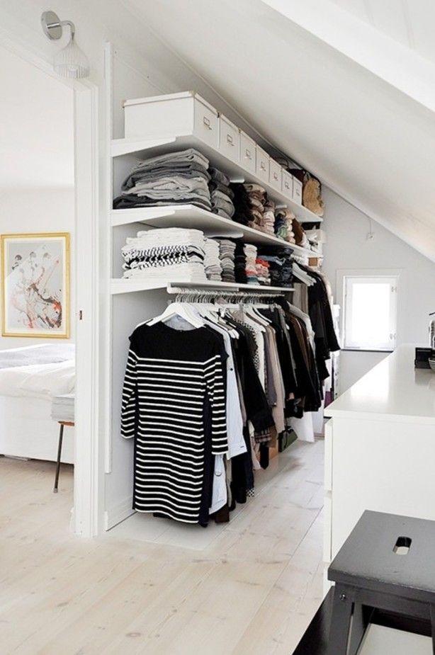 Eenvoudige inloopkast. Hangedeelte onderin. Daarboven simpele planken. Tegenover een kastje van Ikea voor ondergoed, accesoires, etc.