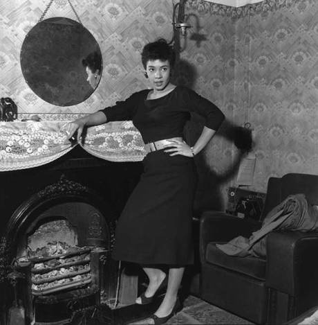 """The Independent reviews a bio of Shirley Bassey: """"Born above a brothel in a rough sea port, a tenth child of mixed-race parentage, she should have had no future beyond the streets or factories. But Shirley Bassey has shown that even a triply underprivileged black Welsh woman could make it to the giddy heights of showbiz. This is the story that John Williams tells in this fascinating book: the way in which she negotiated herself into another world..."""" Here, the Dame herself in 1955"""