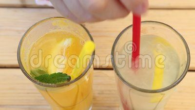 Two glasses of lemonade - oranges in the left and of lemon in right side.