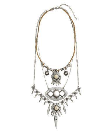 Een kort, multistring halssieraad bestaande uit een koord van imitatiesuède en fijne metalen schakelkettingen. Het sieraad is versierd met metalen hangers in verschillende vormen en kralen en steentjes van metaal, glas en kunststof. Verstelbare lengte 35-41 cm.
