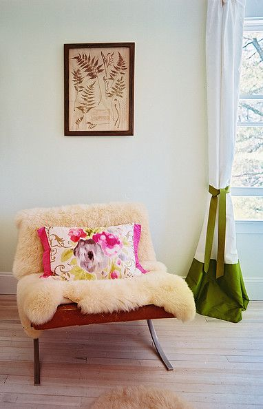 Freshen up cozy shearling with bright spring hues during the warmer months, like this home owner did with grass-green curtains and an antique floral poster.