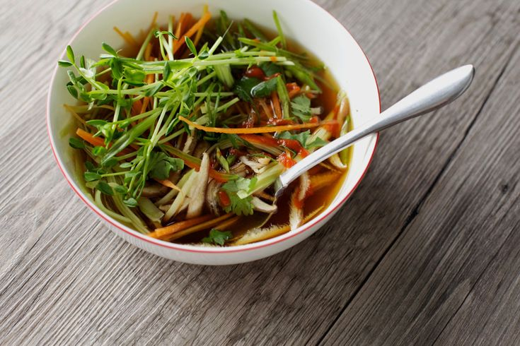 a brothy soup with mushrooms, carrots and other vegetables is topped with sprouts and hot sauce