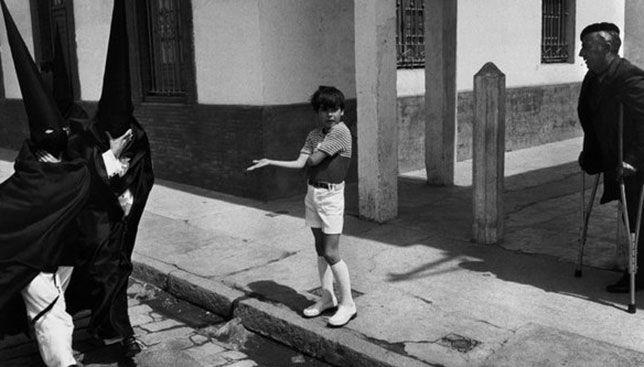 Un niño pide un caramelo a nazarenos de Santa Genoveva en 1973. Fotografía de Josef Koudelka