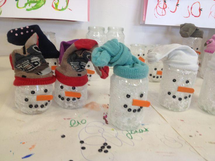 Theelichtje DIY sneeuwman Peuters doen met de borstel lijm op hun potje en dan rollen ze het met juf door de glitters! Oogjes en mond van pailletten, neus van friscostokje. Een sok als muts en klaar!