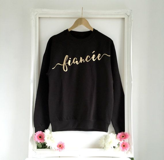 The perfect jumper for the newly engaged!  This black and gold Fiancee sweatshirt will keep you warm and cosy when you're sitting down to plan your wedding!