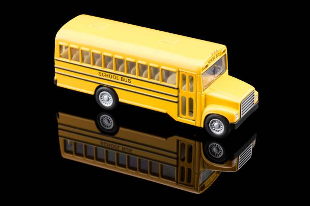 toy school bus with reflection on on black background