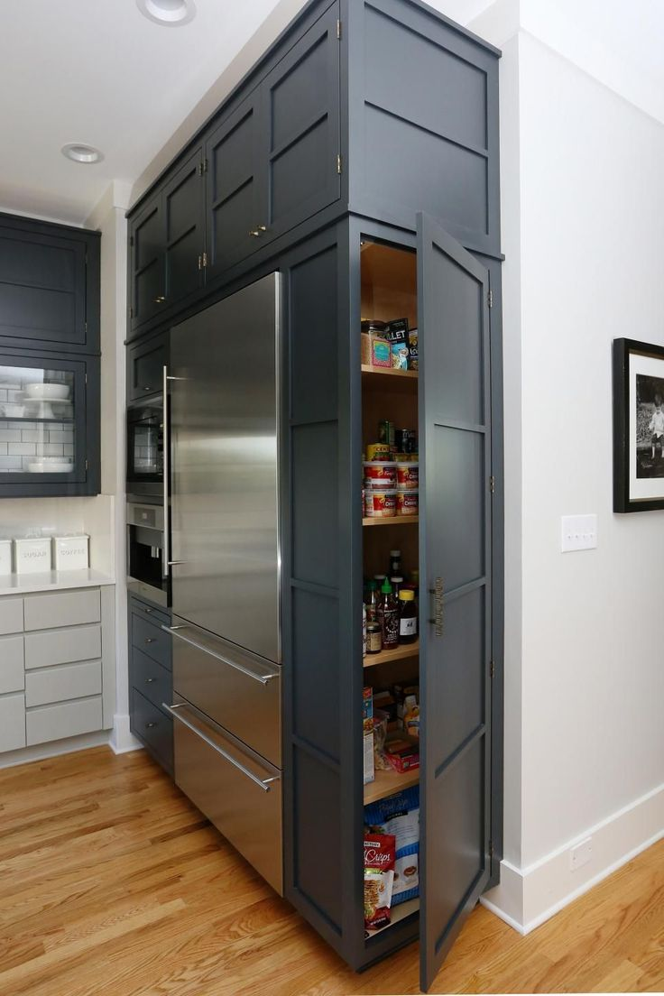 Built-In Pantry in Transitional Kitchen  Making the most of every corner, a pantry is installed in the cabinet that houses the stainless steel refrigerator. Floor-to-ceiling cabinetry also provides tons of much-needed storage in this kitchen, which is truly the heart of the home.