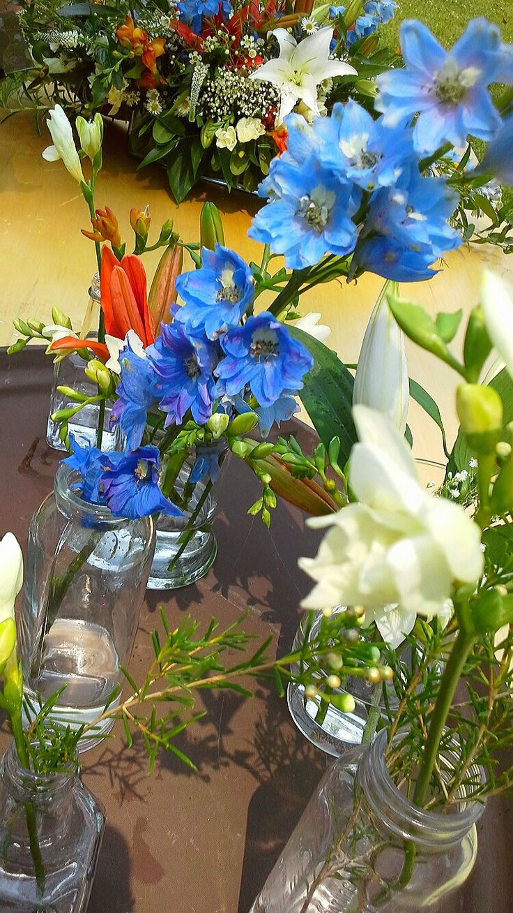 bride's colors of blue delphinium, white and orange freesia in assorted vases; design by Davis Floral Creations