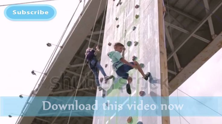 Children climbing rock wall while climbing competition | Stock Footage
