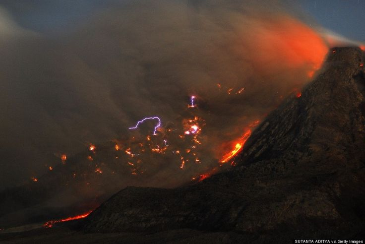 This long exposure photograph taken before dawn on October 14, 2014 shows sparks of lightning, scorching lava flow and giant ash clouds released from the crater during the eruption of Mount Sinabung volcano.