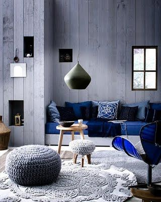 Splashes of royal blue! Love the little nooks/shelves in the wall and the knitted ottoman and stool!