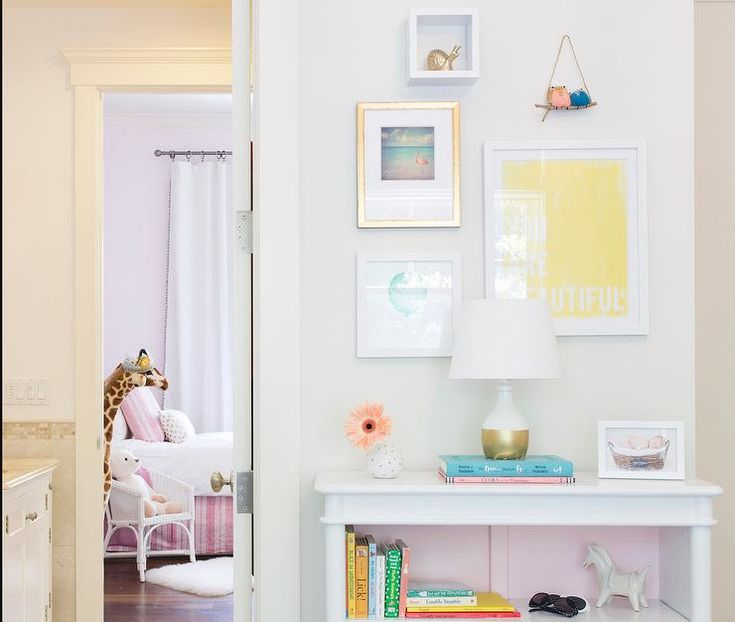 Girl's room features a collection of art over a white bookcase with interior painted pink topped with a gold dipped lamp.
