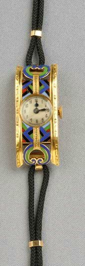 Art Deco Egyptian Revival 18kt Gold and Enamel Wristwatch, the arched rectangular case with polychrome enamel accents and engraved edges, dial with Arabic numeral indicators, and enclosing a manual-wind 15-jewel Emshir Watch Co. movement, 34 mm, case no. 16817.