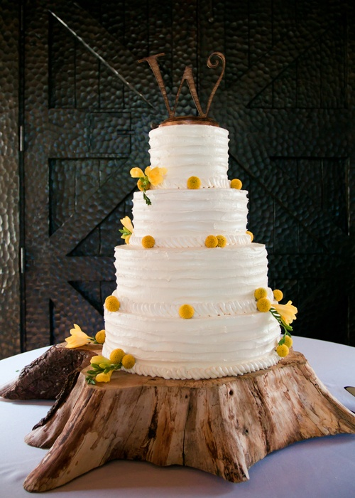Rustic Sculpted wedding cake with yellow billy buttons sitting on a tree stump.