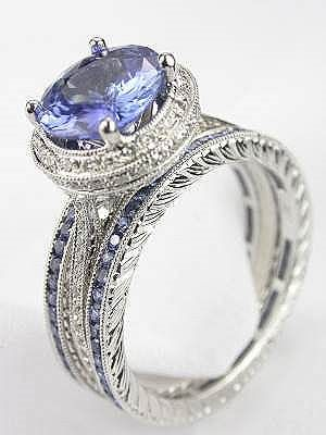 The 18k white gold wedding set includes a blue sapphire and diamond engagement ring as well as a pair of blue sapphire eternity bands. The combined sapphire weight of this wedding ring set is 2.57 carats; the diamonds total 0.30 carats.
