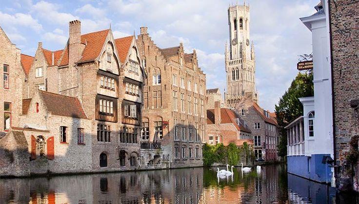 Bruges città medievale con i viali acciottolati, i palazzi e le chiese in pietra. Le case colorate si specchiano nelle acque dei canali. Patrimonio Unesco.