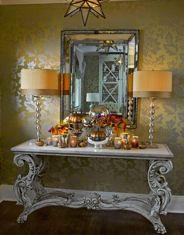The entry is transformed for the Thanksgiving holiday with a display of mercury glass set aglow by the reflective wallpaper from Zoffany, Jamie Young lamps, and a Venetian glass mirror. The console table is by Oly. WREATH: SMITH