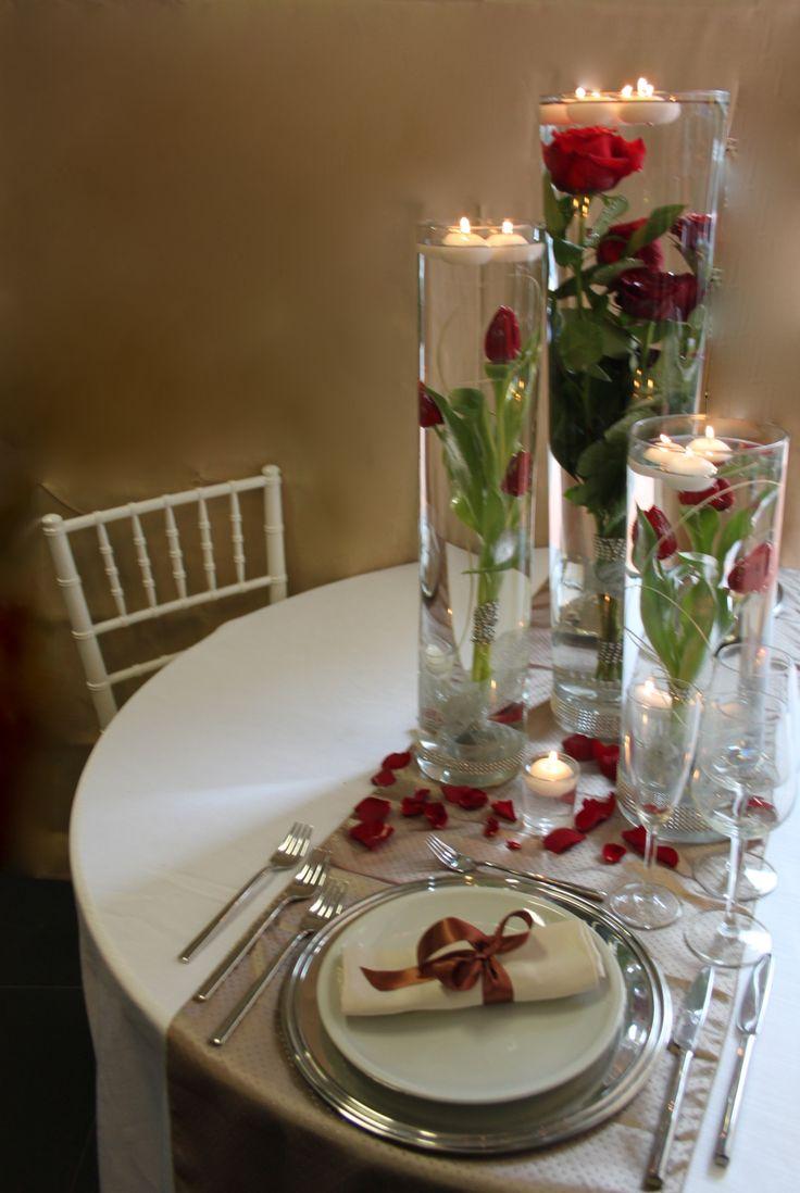 centrotavola con composizione a tre cilindri, rose e tulipani rossi e candele
